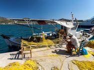 Fischer vor der Kulisse der Insel Poros